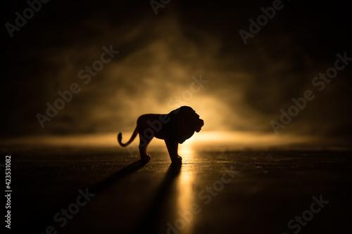 Papel de parede A silhouette of lion miniature standing on wooden table