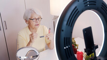 Elderly Woman Having A Video Call While Applying Make Up And Getting Ready For Valentines Day Date. High Quality Photo