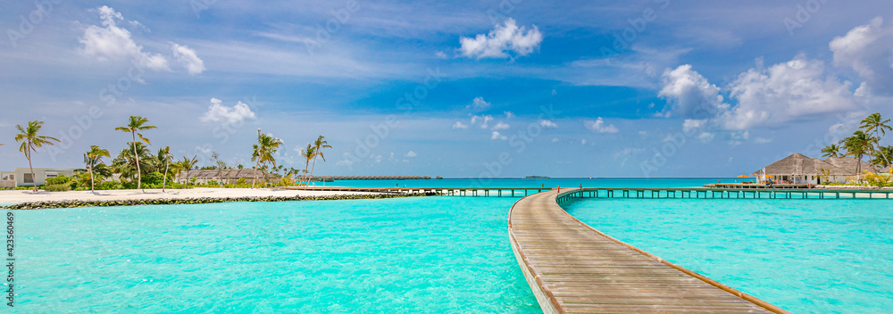 Fototapeta Maldives island, luxury water villas resort and wooden pier jetty. Beautiful sky and clouds and beach background for summer vacation holiday and travel concept. Tourism adventure destination seaside