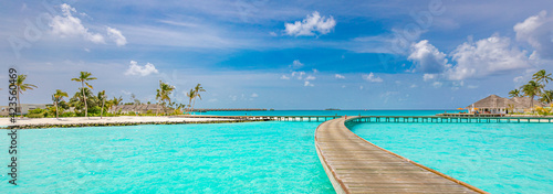 Fototapeta Maldives island, luxury water villas resort and wooden pier jetty. Beautiful sky and clouds and beach background for summer vacation holiday and travel concept. Tourism adventure destination seaside obraz