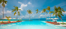 Relax Tourism Landscape. Luxurious Beach Resort With Swimming Pool And Beach Chairs Or Loungers Leisure Lifestyle, Under Umbrellas, Palm Trees, Blue Sky. Summer Travel And Vacation Background Concept