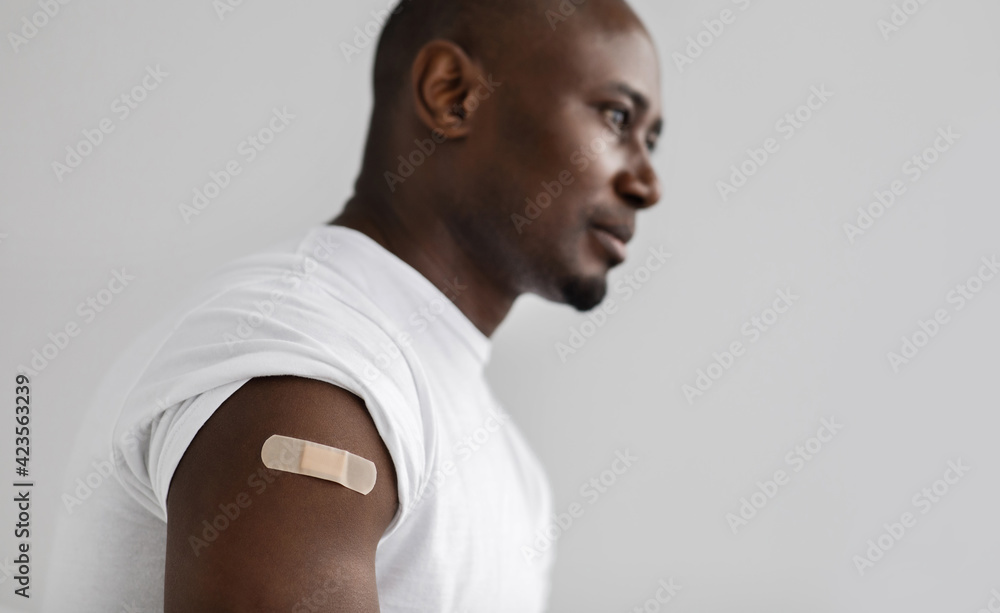 Fototapeta Coronavirus, covid-19 vaccine concept. Black man with an adhesive bandage on shoulder after injection