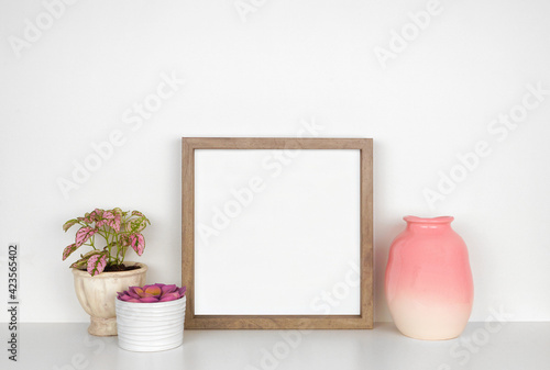 Fototapeta Mock up wood square frame with pink houseplants and vase. White shelf against a white wall. Copy space. obraz
