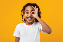 African American Girl Smiling, Looking At The Camera Through Fingers