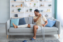 Young African American Guy With Plastered Leg Sitting On Sofa, Leaning On Crutches At Home