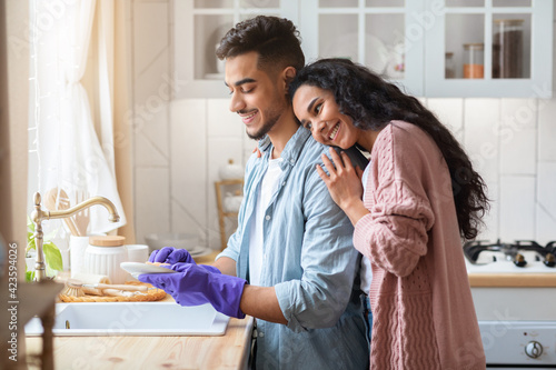 Fototapeta Young Arab Husband Washing Dishes After Lunch, Helping Wife With Domestic Chores obraz