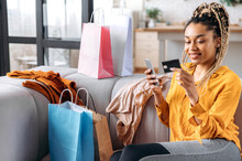 Beautiful Satisfied African American Girl With Dreadlocks Sits On Sofa At Home, Using Smartphone And Credit Card For Online Payments, Nearby Many Paper Bags And New Clothes, Online Shopping, Smiling