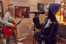Young Woman Singing In Microphone With Her Colleague Playing Guitar In The Background During Their Rehearsal