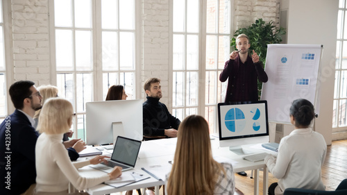 Foto Confident young Caucasian male coach or trainer make whiteboard presentation for diverse employees in office