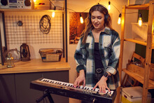 Young Musician In Headphones Playing On Electric Piano In The Studio