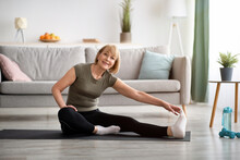 Domestic Workout. Cheerful Senior Lady Stretching Her Leg On Sports Mat In Living Room, Empty Space