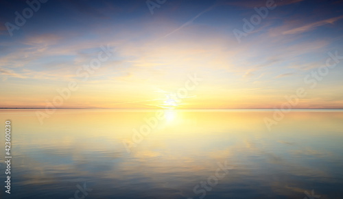 Baltic sea after the rain. Dramatic sunset sky, glowing pink and golden clouds, symmetry reflections in the water. Abstract natural pattern, texture, background. Picturesque panoramic scenery