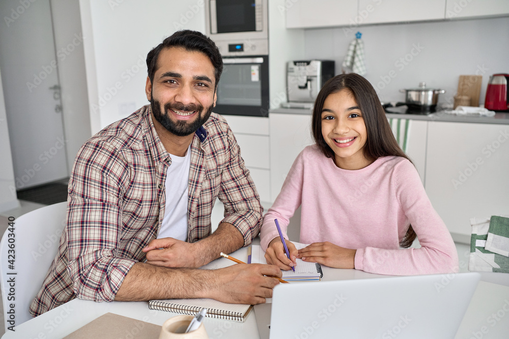 Fototapeta Happy young indian parent father helping teenage child daughter distance learning online together at home. Teen school kid girl studying in kitchen with dad looking at camera sitting at kitchen table.