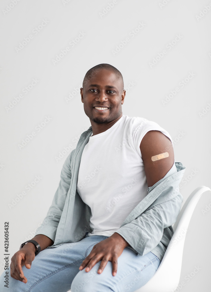 Fototapeta Happy black man showing his arm with an adhesive bandage after injection of vaccine.