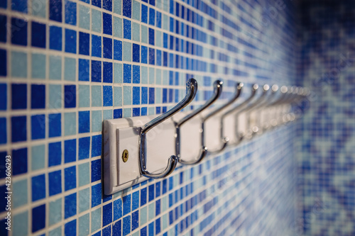 Obraz na plátně Metal hanger hooks on blue tiled wall