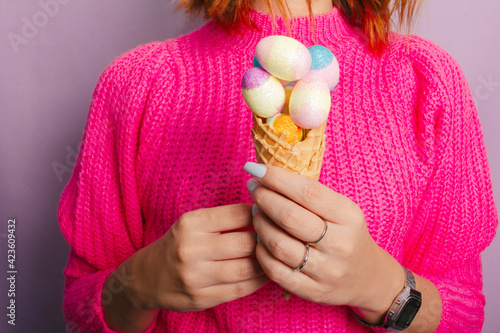 Obraz Female hand holding colorful ice cream made with chocolate eggs. Easter. Lilac background. - fototapety do salonu