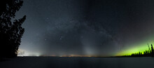 Panoramic View Of A Star Filled Night Sky With The Milky Way And Some Aurora Above A Snow Covered Lake.  The Zodiacal Light Can Also Be Seen On The Horizon.