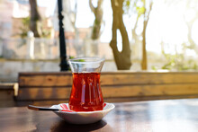 Glass Of Traditional Turkish Tea On A Wooden Table Of Street Cafe On Sunny Spring Day In Istanbul, Turkey.