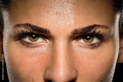 Fototapeta Inspirational close up of determined and passionate athlete, confident powerful eyes staring intense with conviction during workout exercise	 obraz