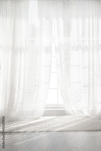 Obraz Backlit window with white curtains in empty room - fototapety do salonu