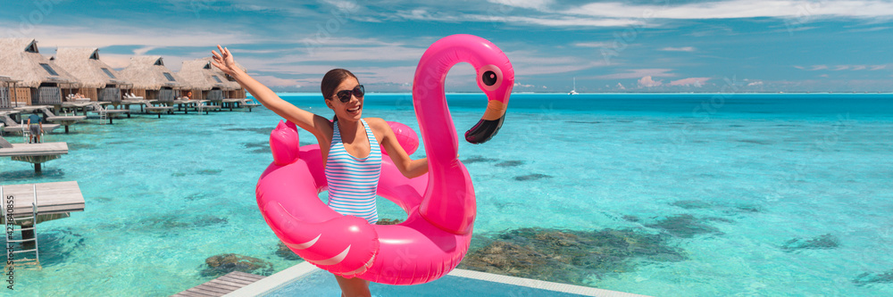 Fototapeta Summer vacation girl having fun jumping with pink flamingo pool float in swimsuit at luxury hotel. Funny travel holiday tourist woman jumping with open arm excited banner panoramic.