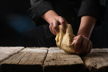 Chef Prepares Dough With Rolling Pin On Black Background.Culinary Pastries, Dough Preparation. Freezing In Motion. Recipe Book On A Black Background For Advertising Baking And Restaurant Business
