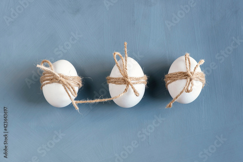 Fototapeta Three Easter eggs decorated with twine on a gray background. Easter card in scandinavian eco-friendly style with copy space obraz