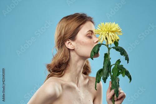 Foto Beautiful nude woman shoulders yellow flower charm blue background