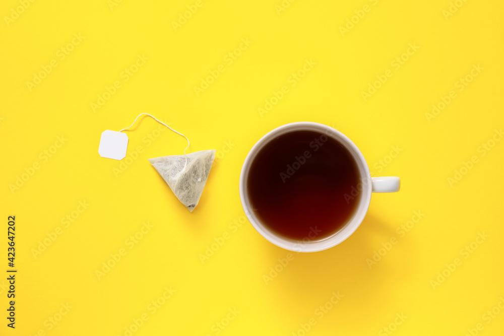 Fototapeta Cup of hot beverage and tea bag on color background - obraz na płótnie