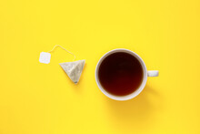 Cup Of Hot Beverage And Tea Bag On Color Background