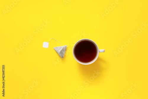 Fototapeta Cup of hot beverage and tea bag on color background obraz na płótnie