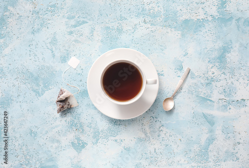 Fototapeta Cup of hot aromatic black tea on color background obraz