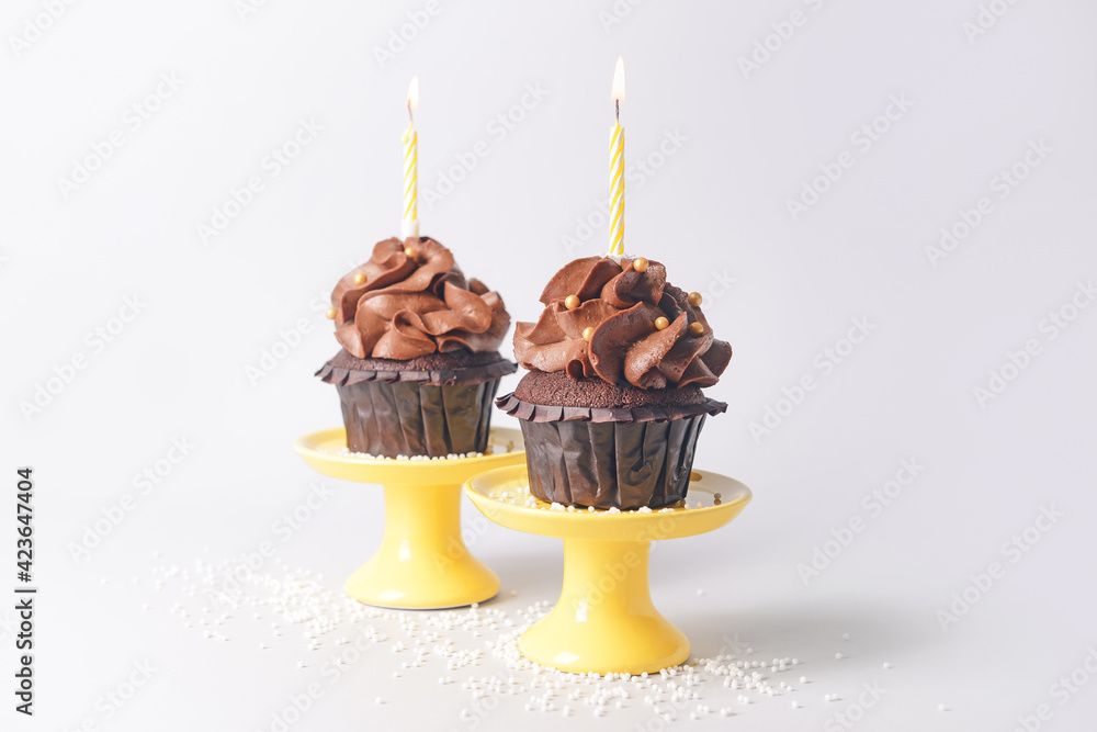 Fototapeta Tasty chocolate cupcakes with candles on light background