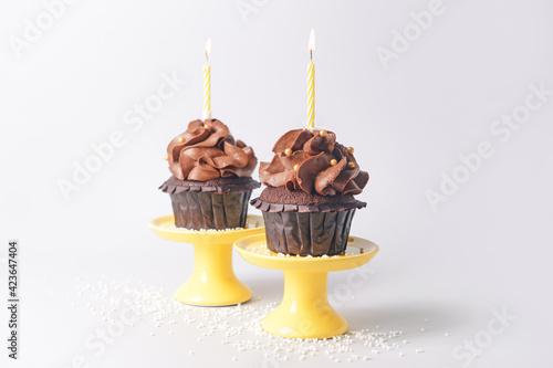 Obraz Tasty chocolate cupcakes with candles on light background - fototapety do salonu