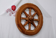 Vintage Wooden Wheel From Cart As Decor On The Wall. Embroidered Canvas With Flowers. People's Needlework.