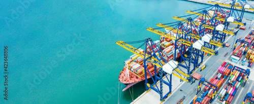 Fototapeta Aerial top view Cargo operations on container ship in port. Business logistic commercial intermodal freight transport in import export, Cargo ship of international at seaports in the world obraz