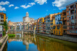 Girona, Spain - July 28, 2019: Beautiful colorful riverside houses in the Jewish quarter of Girona city in Catalunya, Spain, with Girona Cathedral in the background