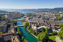 Aerial View Of The Limmat River That Flow Through The Zurich City Center By The National Museum, The Train Station And The Old Town To Finish In Lake Zurich On A Sunny Summer Day