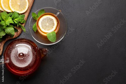 Fototapeta Herbal tea with mint and lemon. Tea cup and teapot