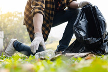 Man's Hands Pick Up Plastic Bottles, Put Garbage In Black Garbage Bags To Clean Up At Parks, Avoid Pollution, Be Friendly To The Environment And Ecosystem