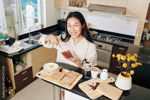 Fényképezés Pretty smiling young Vietnamese woman making sandwich with whole wheat bread and