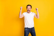 Photo of happy cheerful crazy mature man raise fists winner celebrate isolated on yellow color background