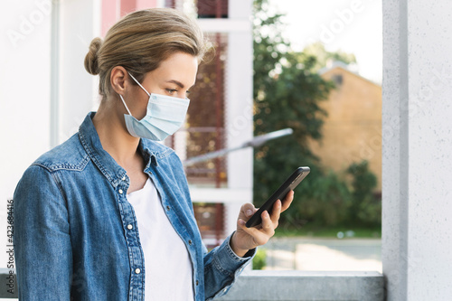 Woman with a prevention mask on her face is using smartphone