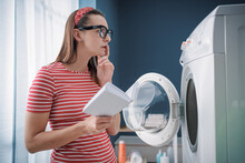 Woman Learning How To Use Her Washing Machine