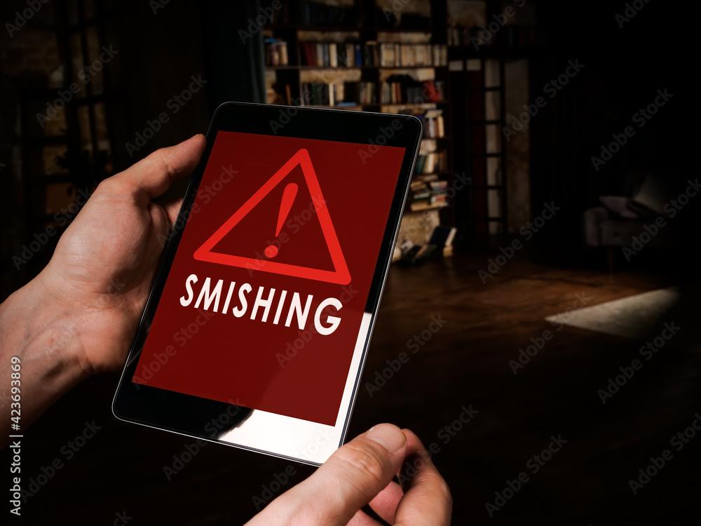 Fototapeta Smishing alert concept. Hands hold tablet with message.