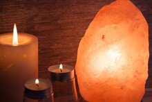 Himalayan Salt Lamp With, Candles In Dark Room. Spa, Relax Concept.