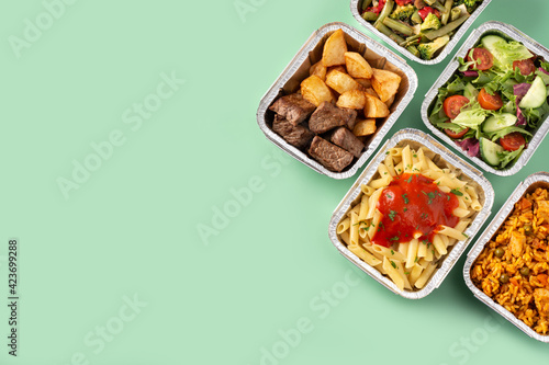 Take away healthy food in foil boxes on green background. Copy space