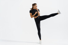 Motivation And Sport. Determined Sportswoman Athletic Fit Body, High Kick, Raising Legs, Punching Air, Do Leg Kick Tae-bo Practice Exercises, Smiling Pleased, Wearing Black Activewear For Fitness