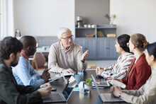 Portrait Of Modern Senior Businessman Talking To Group Of People During Meeting At Table In Office