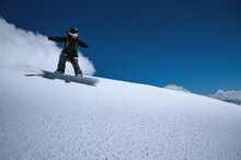Young Sportswoman Woman On A Snowboard Rolls Down A Snowy Slope Against A Blue Sky On A Sunny Day